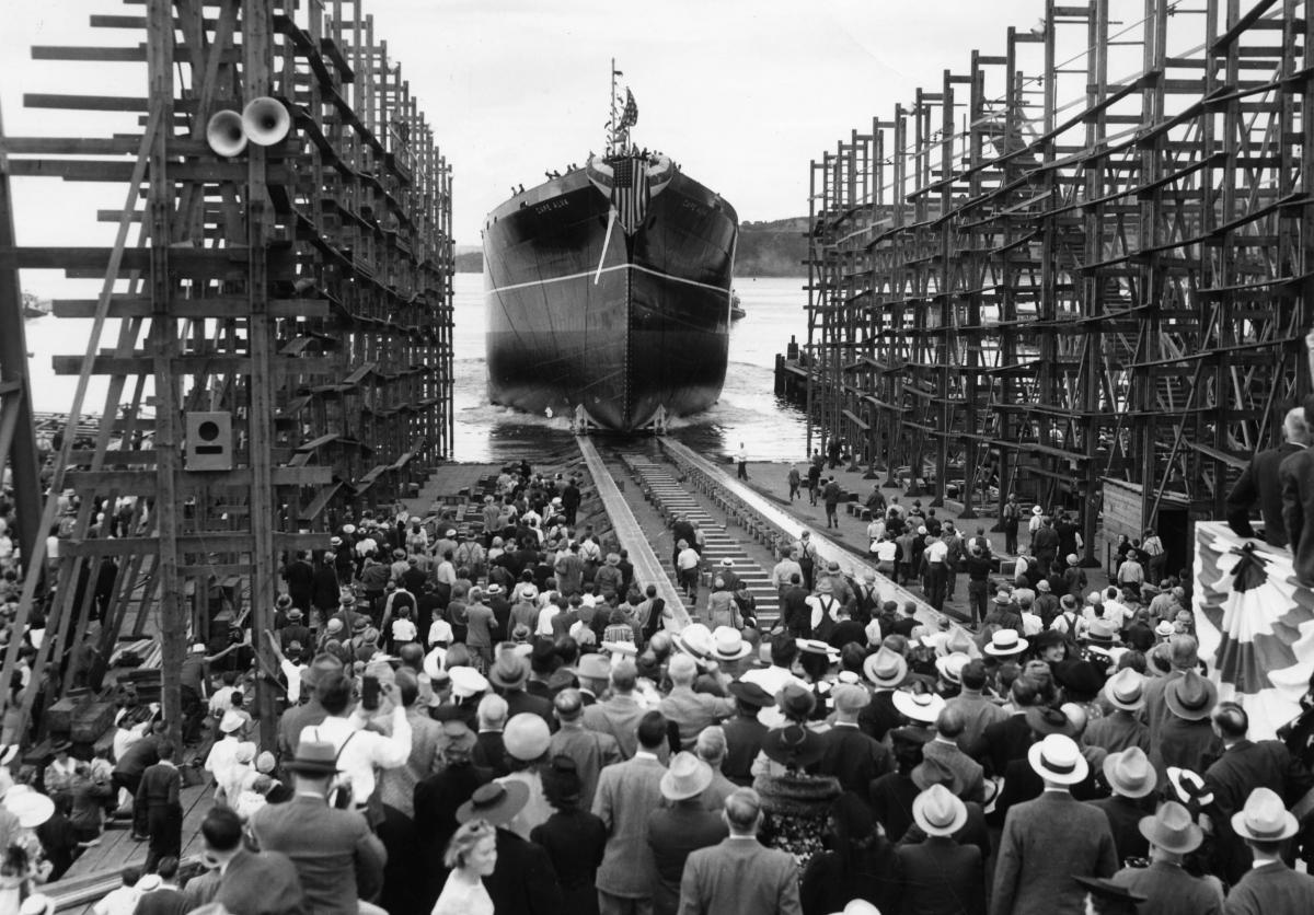 historical photo of people gathered to watch a vessel being launch