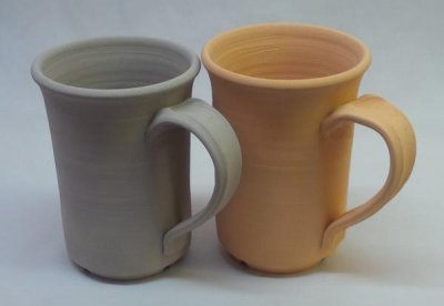 A dried terra cotta mug on the left, bisque fired to cone 06 on the right