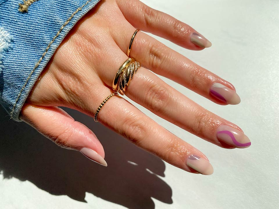 hand with nail art decals and wearing jean jacket