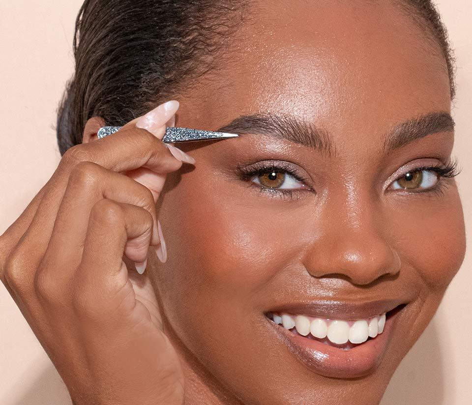 Woman using JAPONESQUE® tweezers to groom eyebrows