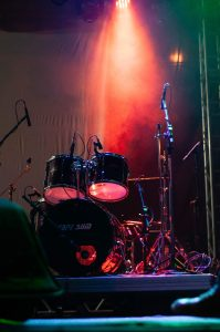 Drum set on stage with red light beaming down onto it