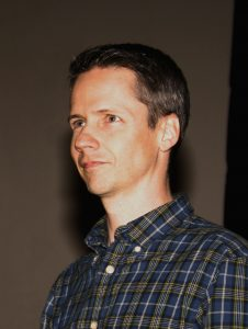 Photo of John Cameron Mitchell - a white representing male with short brown hair. He is wearing a blue and green plaid shirt and facing to the left of the photo, about half way between a forward facing stance and a profile stance.
