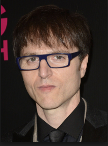 Photo of Stephen Trask - a white representing male with short brown hair. He is wearing dark blue thick-framed glasses and is facing the camera. You can see the top of his suit which is a black shirt, black coat, and black tie.