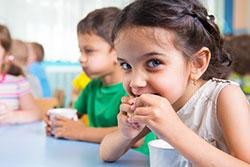 Cute little girl eating snack