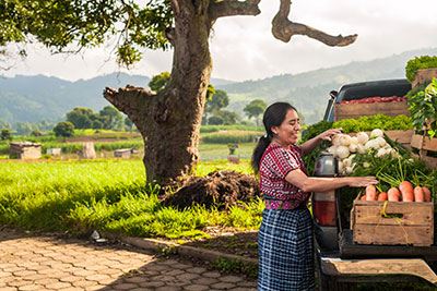 Indigenous woman with her truck full of vegetables