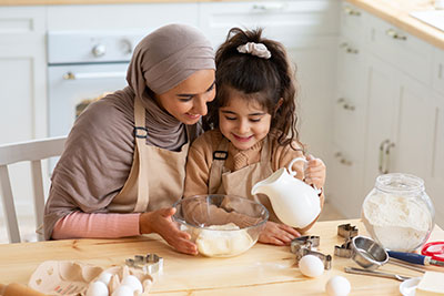 Mom Baking With Her Little Daughter In Kitchen