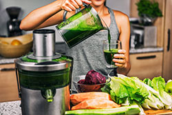 Woman juicing making green juice
