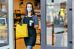 Young woman with face mask giving coffee to customer