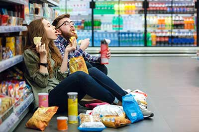 Couple sitting on the supermarket floor and eating chips