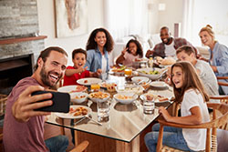 Families taking selfie as they enjoy meal