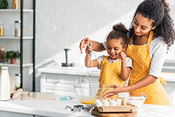 Mother and daughter whisking eggs