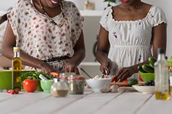 Two african american women cooking in kitchen
