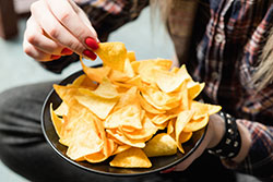 Woman eating chips from a bowl
