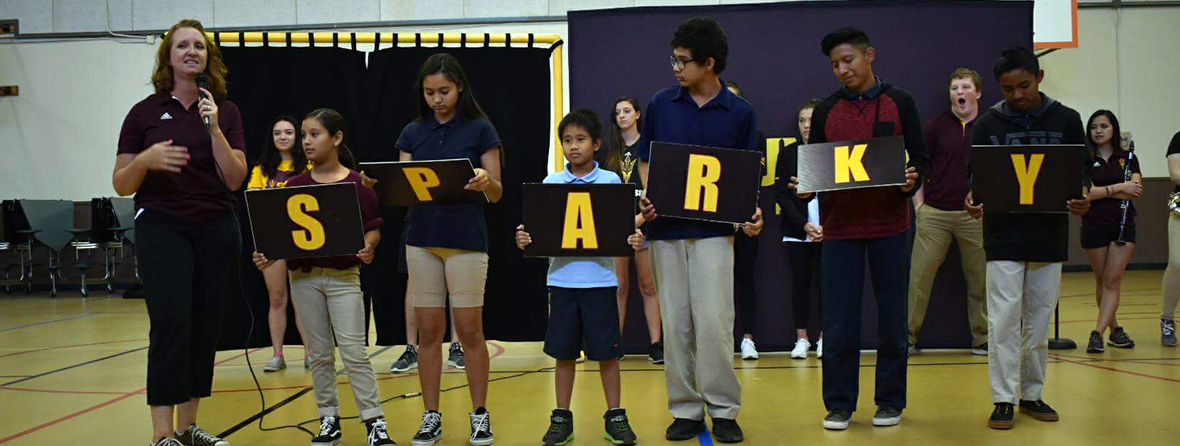Teacher with microphone along with students holding up SPARKY letters