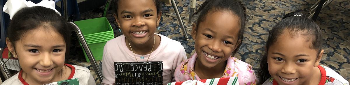 Four smiling female Oakwood Academy students