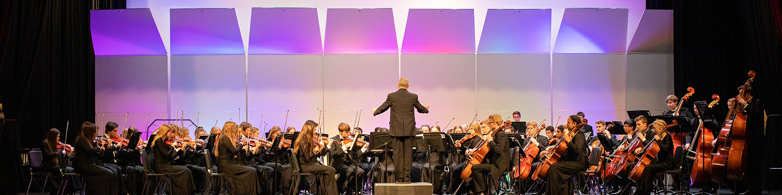 Orchestra Performance on stage with purple lighting