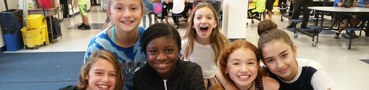 Students pose together in a cafeteria