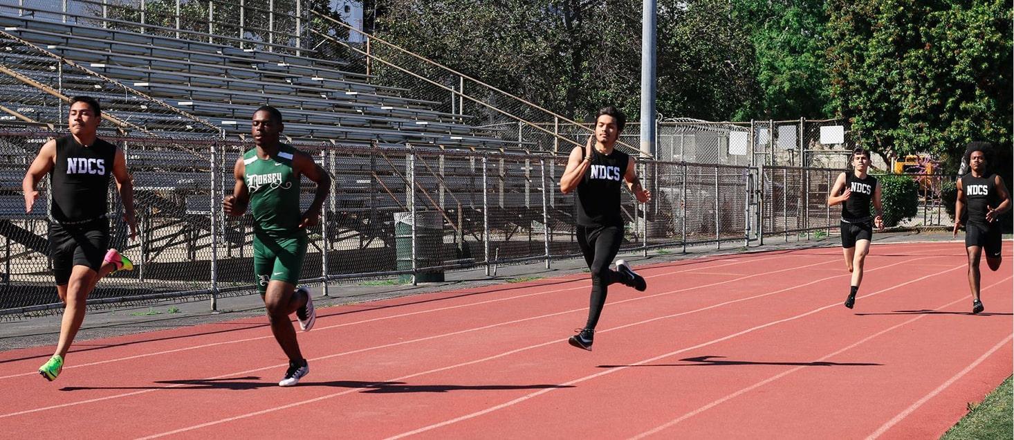 track team members running on track
