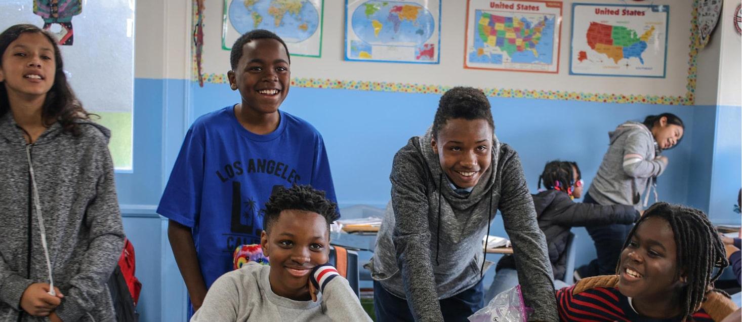 students gathered around desks smiling
