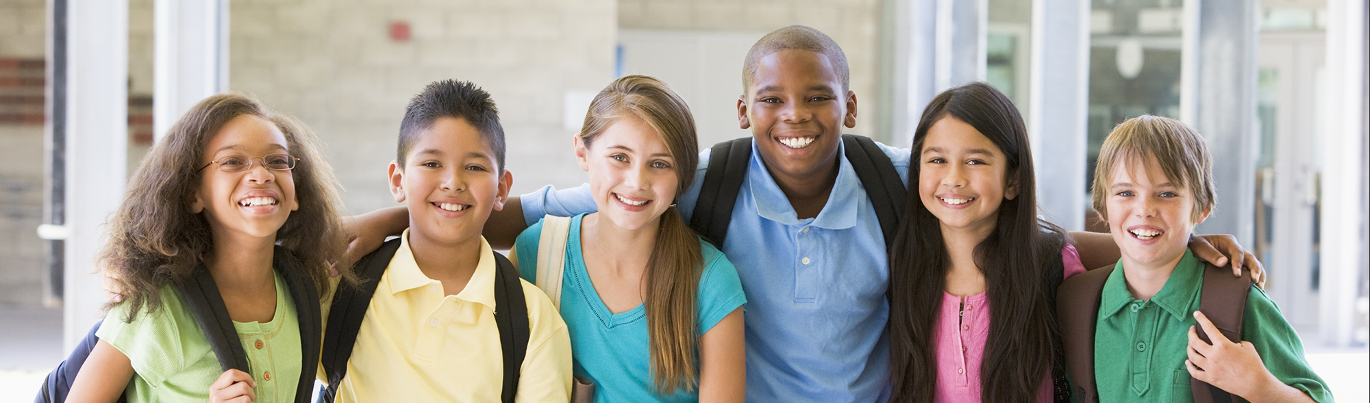 students with backpacks standing with arms around each other