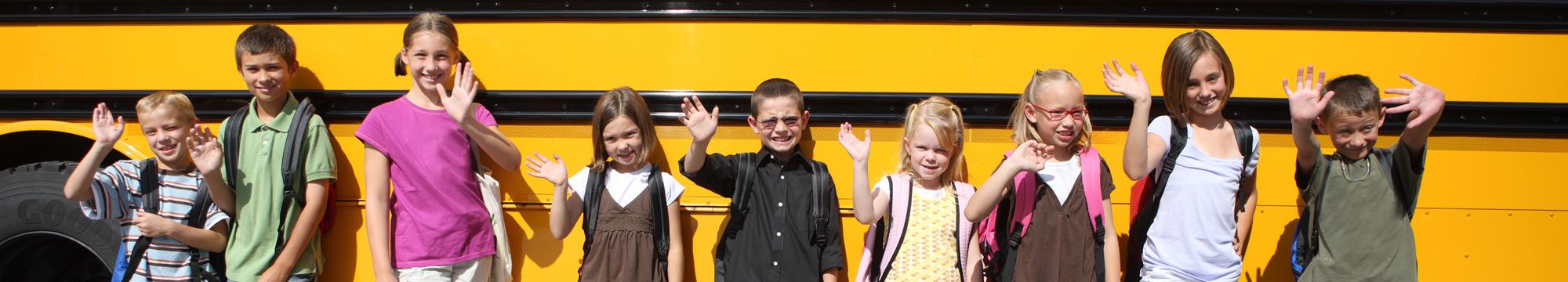 students standing in front of school bus
