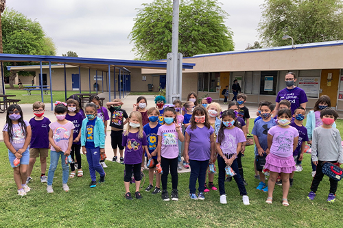 Young students wearing purple outside