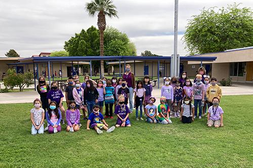 Students in purple posing outside
