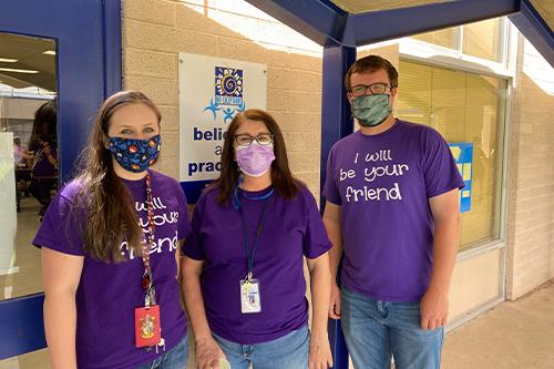 Three staff members wearing purple shirts