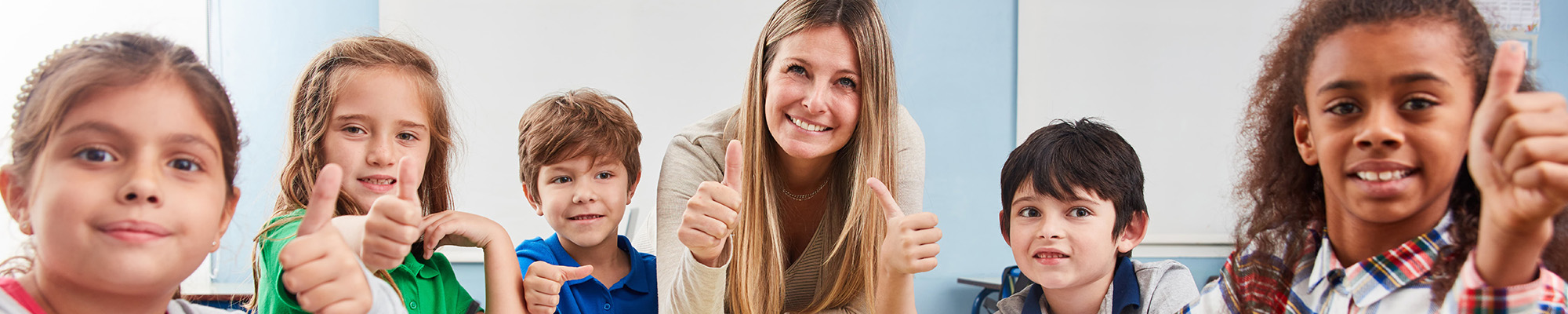 Teacher sitting at a table with happy students giving a thumbs up