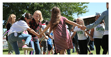 Students playing with hula hoops and holding hands at the elementary pep rally