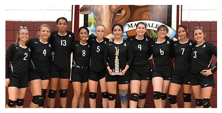 Female volleyball team posing with a trophy