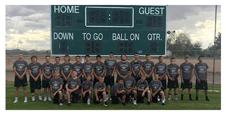 Football team poses in front of a scoreboard