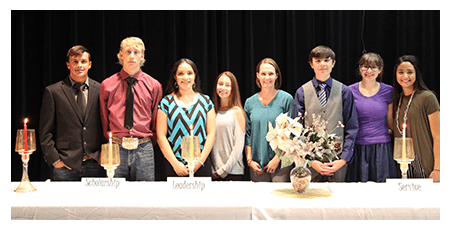 Students posing together behind a table during NHS inductions