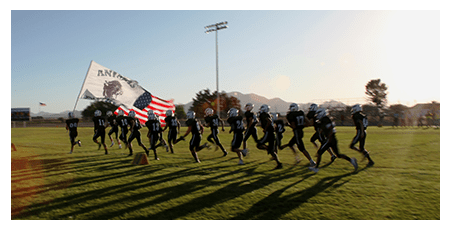 Students running together outside with an American flag and an Animas flag