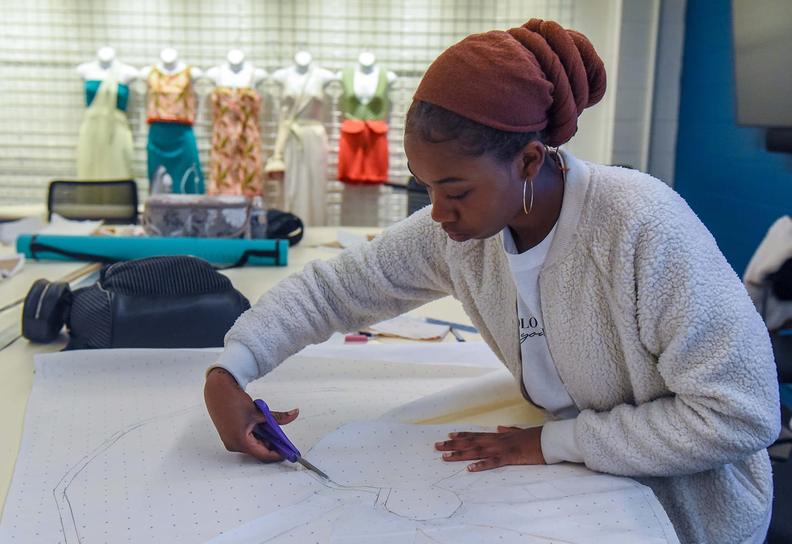 A student cutting out a clothing pattern outline
