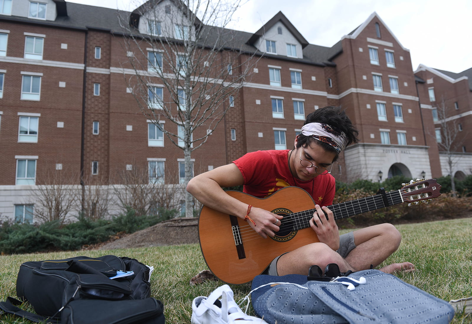 A student playing guitar on the lawn of Belmont University