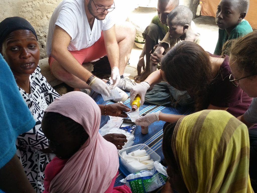 Pardonnez le visage d'Amina mais ici les volontaires font le soin au daara/Excuse Amina's face but here the volunteers are disinfecting sores of the children in the daara