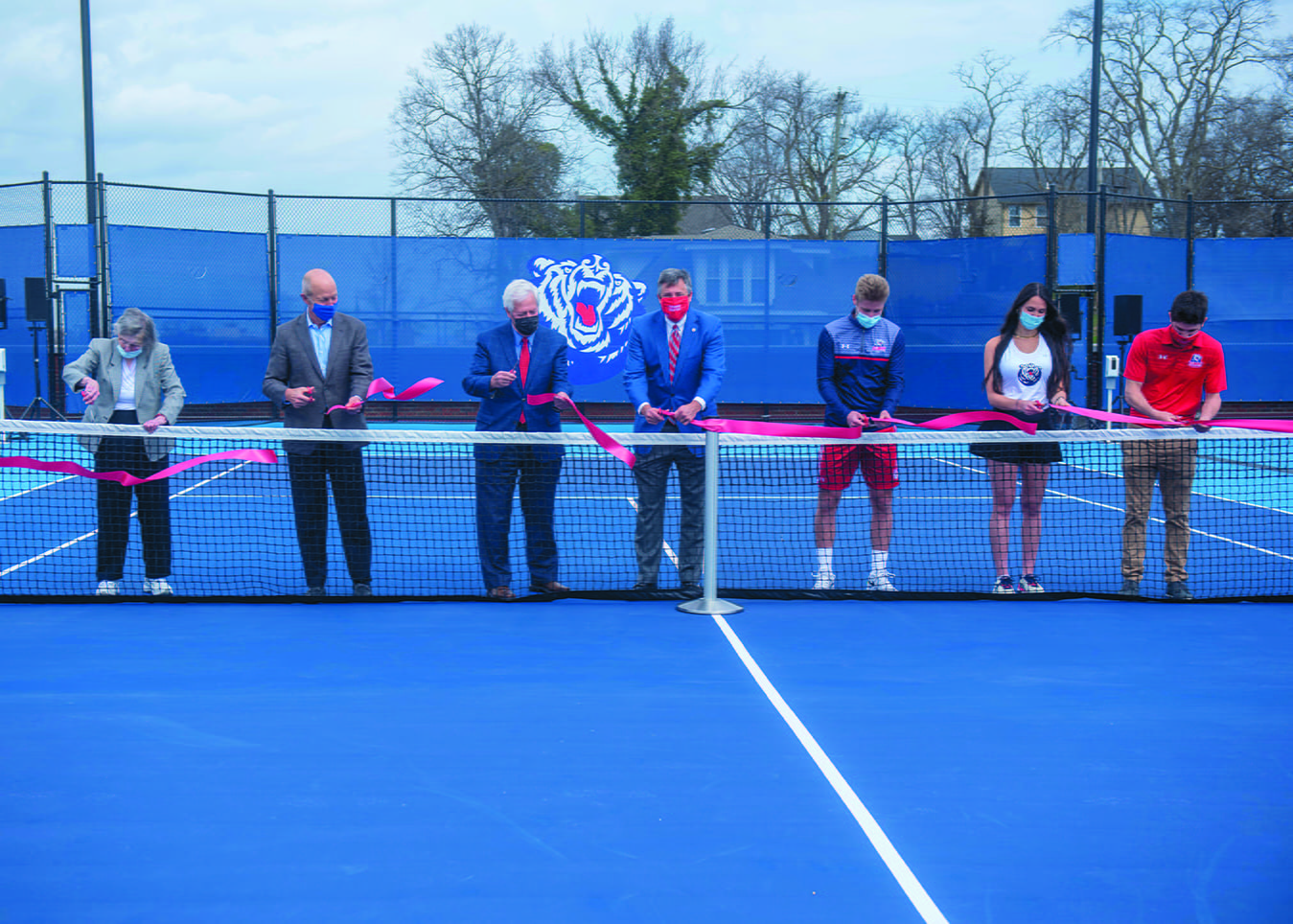 Pat Johnson, Bill DeLoache, Dr. Fisher, Scott Corley, Marko Illic, Somer Henry and Mauricio Antun cut the ribbon during the ceremony opening Belmont's new rooftop tennis facility at Belmont University in Nashville, Tennessee, March 10, 2021.