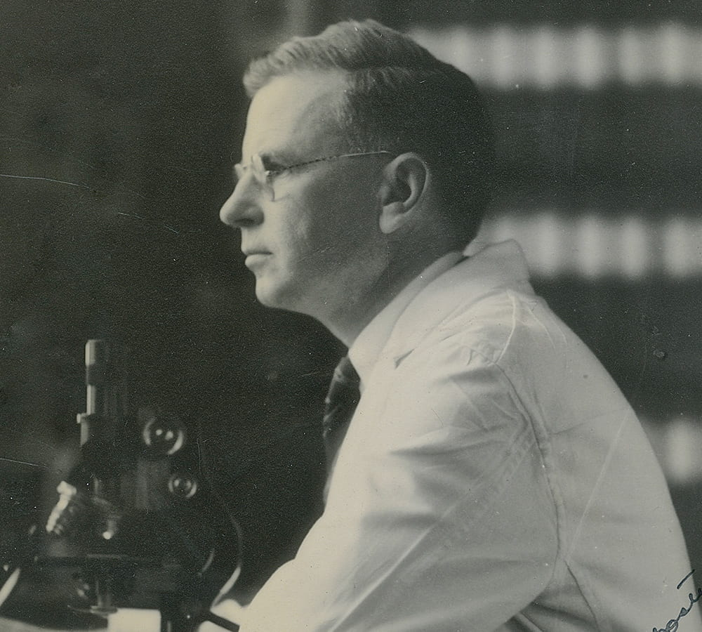 Ernest Goodpasture working with a microscope