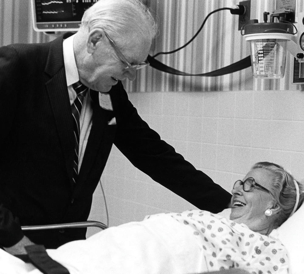 Thomas Frist Sr. at a bed talking to a patient