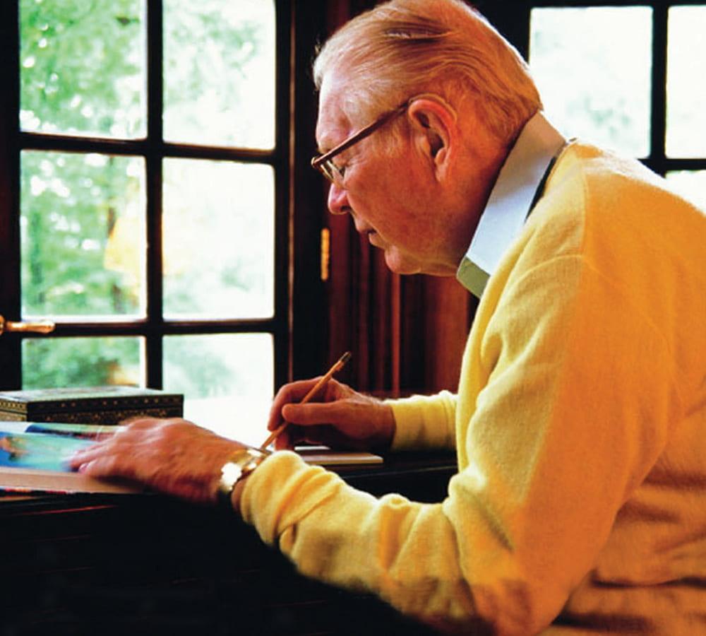 Thomas Frist Sr. writing at a desk