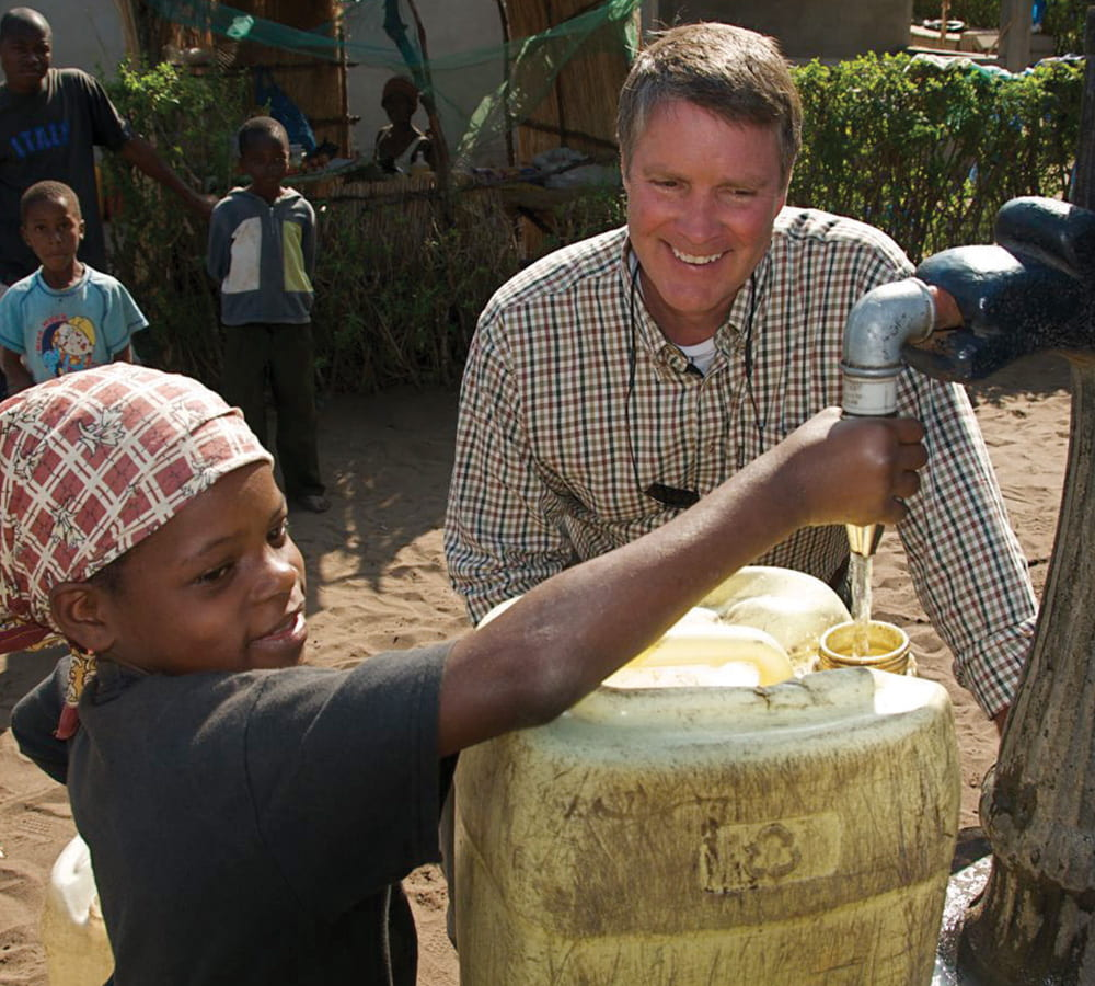 Bill First helps a child with a water tap