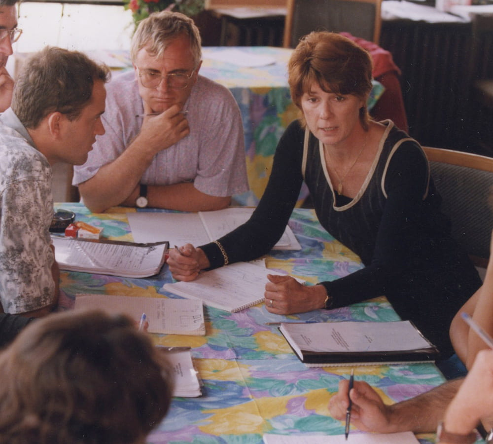 Carol Etherington at a table having a meeting with several others