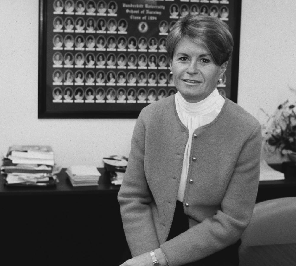 A profile photo Colleen Conway Welch sitting on a desk