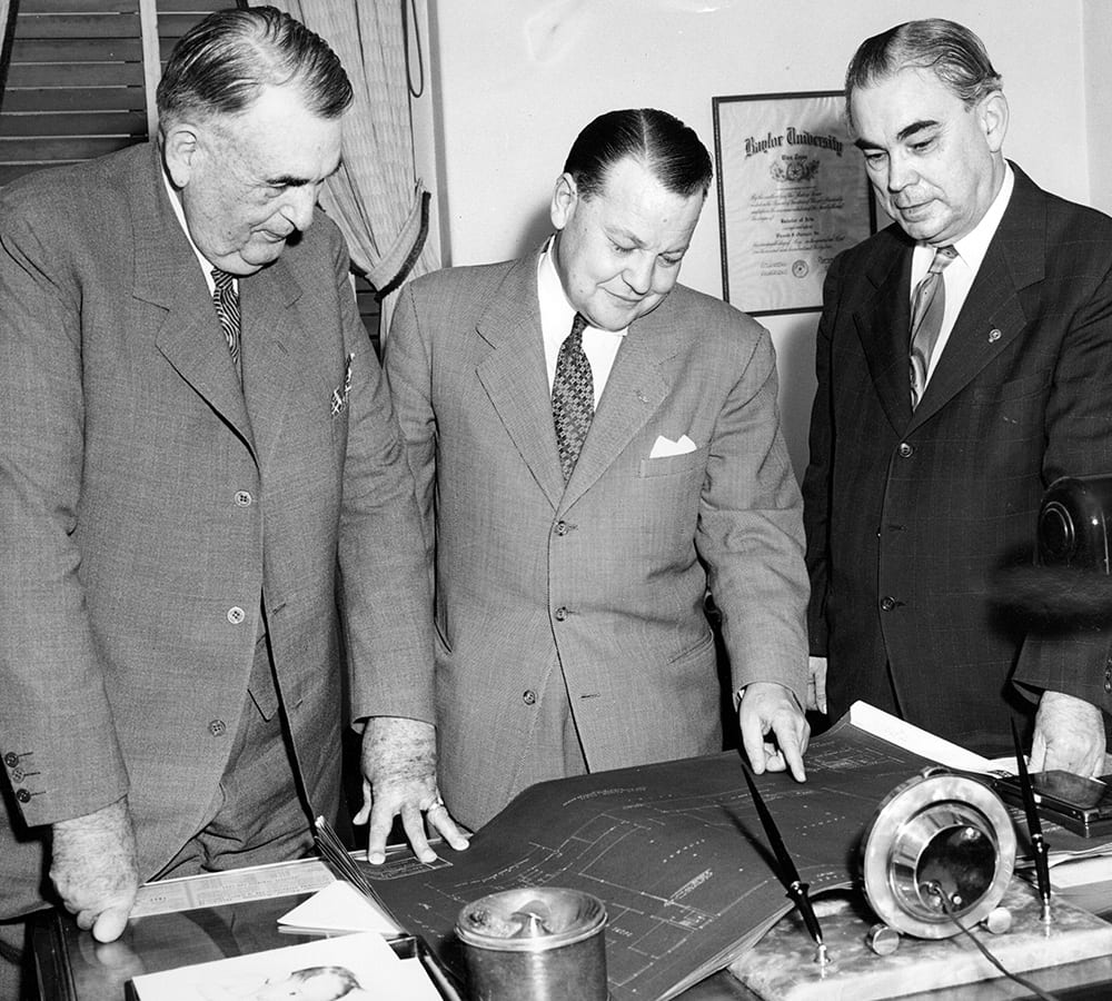 Frank Groner looking at blueprints with two colleagues
