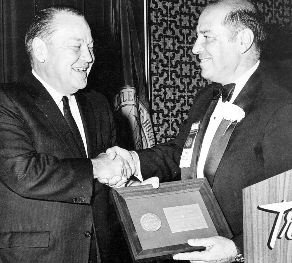 Frank Groner receiving an award and shaking a colleagues hand