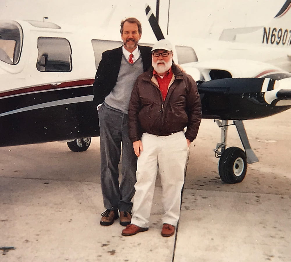 Lynn Massingale with a friend in front of a plane