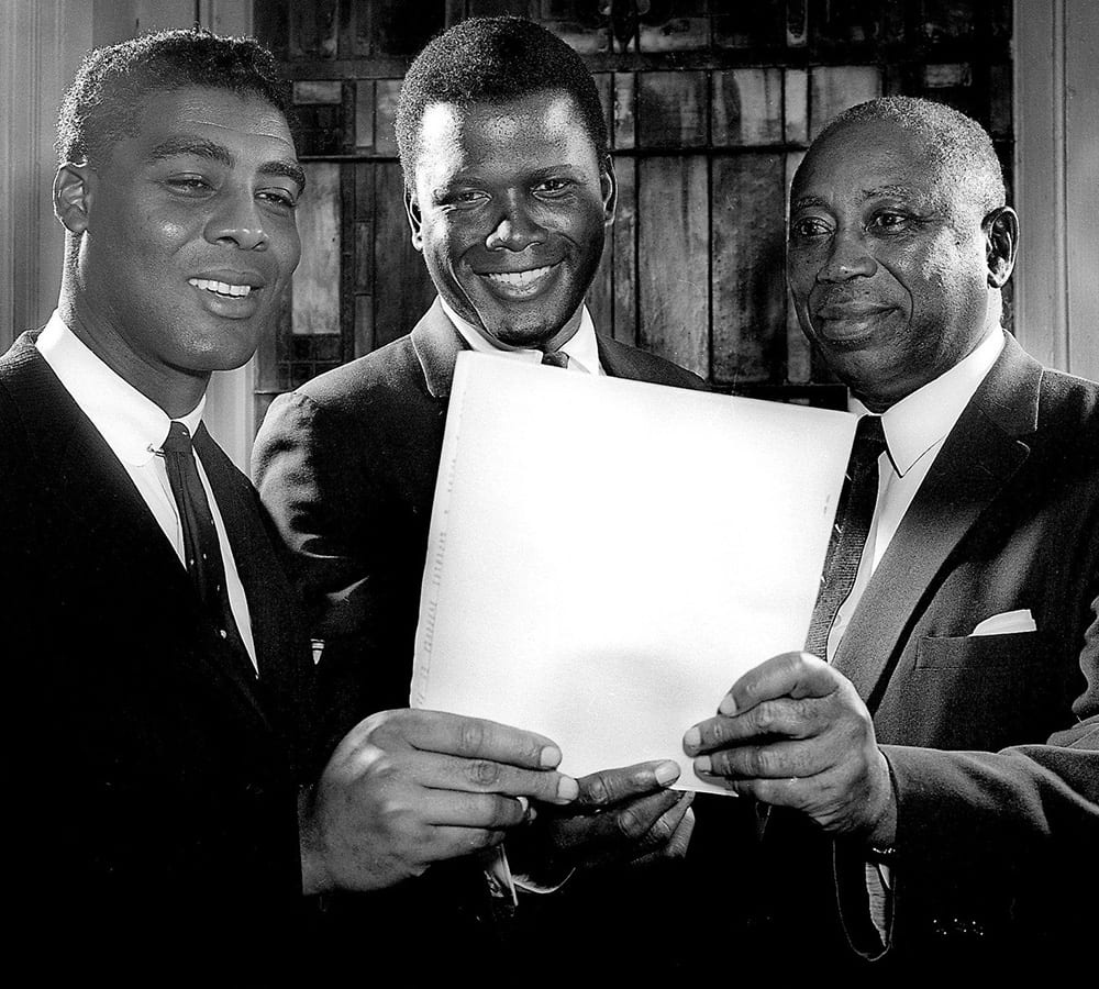 Matthew Walker Sr. holding up a piece of paper with two others