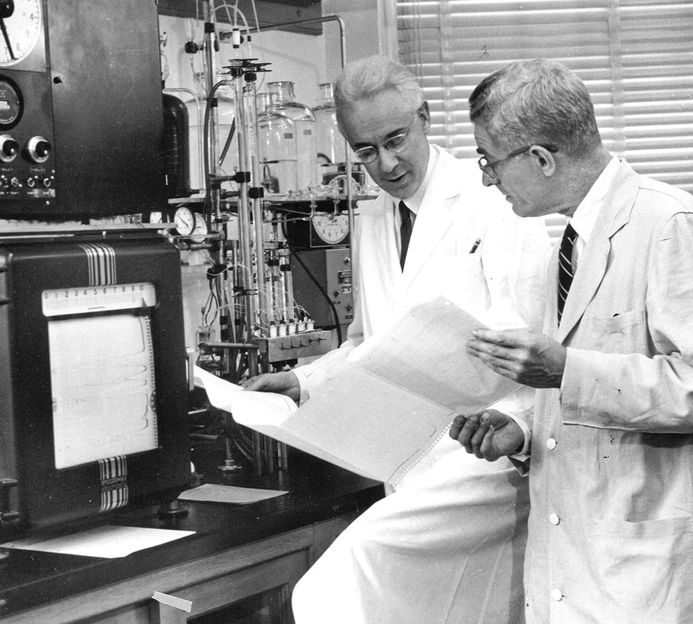 Stanford Moore looking at results with a colleague in a laboratory