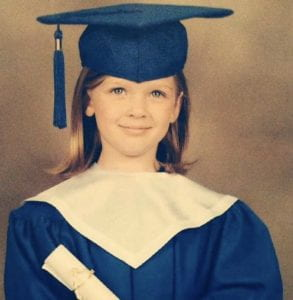 Alexandra graduating from kindergarten because she learned to read and write.